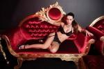 stripteaseuse pose en lingerie noir sur un canapé velours rouge avec dorure