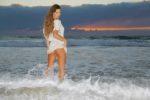 Stripteaseuse pose en robe blanche à la plage en Aquitaine