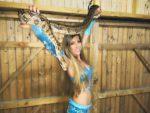 fille en tenue orientale qui tient un gros python reptile en Pays de la Loire