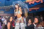 Échassière en tenue sexy qui tient un parapluie dans une discothèque